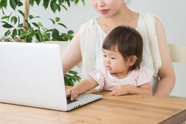 ママの膝に座ってパソコンに手を伸ばす子供の写真