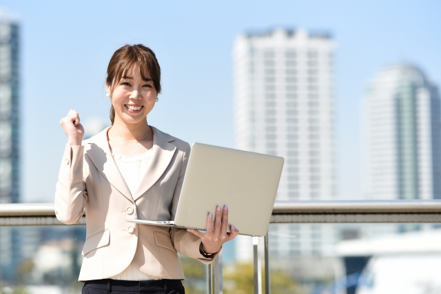 パソコンを手に持ってガッツポーズをする女性の写真
